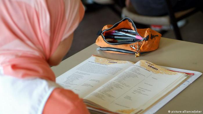 Ein Mädchen mit Kopftuch liest in einem Lehrbuch