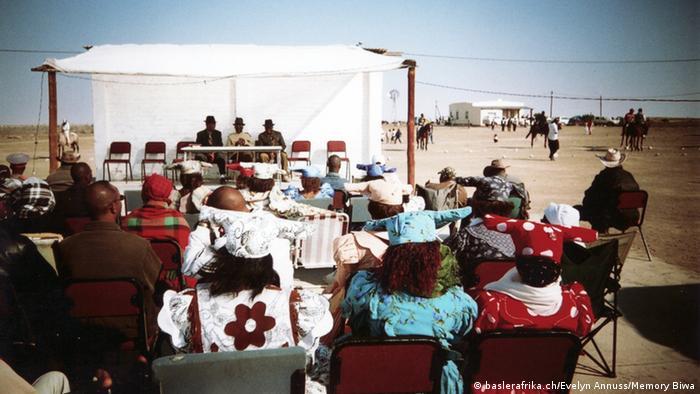 Versammlung mit Frauen in traditionellen Gewändern. Foto: baslerafrika.ch/Evelyn Annuss/Memory Biwa.