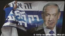 TEL AVIV, ISRAEL - MARCH 17: An Israeli man hangs a poster of Prime Minister Benjamin Netanyahu at his election campaign headquarters on election day on March 17, 2015 in Tel Aviv, Israel. Israel's general election voting has begun today as polls show on that Chairman of the Zionist Union party, Isaac Herzog stands as the only rival to current Prime Minister Benjamin Netanyahu. (Photo by Lior Mizrahi/Getty Images)