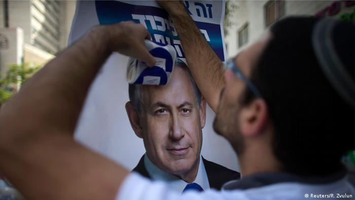 A Likud supporter hangs up a poster of Netanyahu