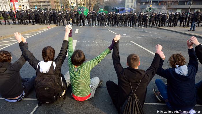 протестующие сидят на асфальте