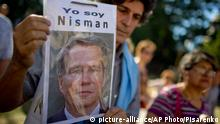 A demonstrator holds a sign of late prosecutor Alberto Nisman that reads in Spanish I am Nisman during an act to demand justice after more than a month after his death, outside the court house in Buenos Aires, Argentina, Wednesday, March 18, 2015. Nisman was found dead in his bathroom on January 18, on the eve of congressional hearings where he was due to present his accusations against President Cristina Fernandez of shielding Iranian officials from prosecution over the 1994 bombing of a Buenos Aires Jewish centre. (AP Photo/Natacha Pisarenko)