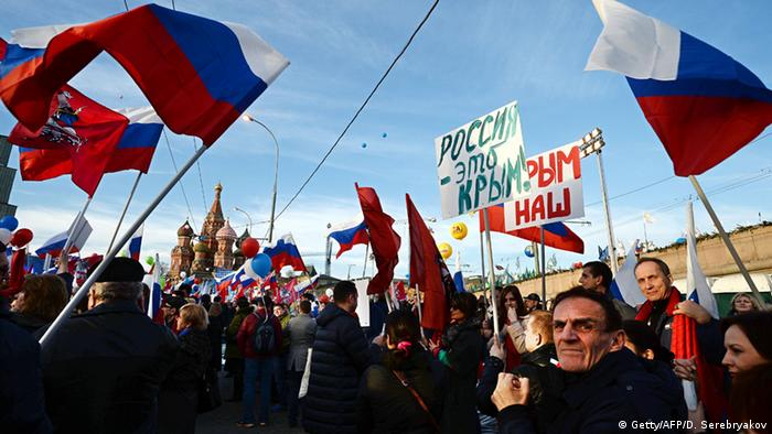 People take part in a rally and a concert by the Kremlin Wall in central Moscow on March 18, 2015, to mark one year since Russia's President Vladimir Putin signed off on the annexation of Crimea in a epochal shift that ruptured ties with Ukraine and the West.