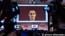 Der US-amerikanischer Whistleblower Edward Snowden ist am 18.03.2015 in Hannover (Niedersachsen) während einer Videoliveschalte auf einem Monitor zu sehen. Foto: Ole Spata/dpa eingestellt von mak