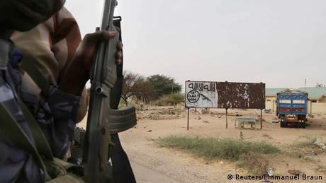 A Chadian soldier rides in a car past a signpost pained by Boko Haram (Reuters/Emmanuel Braun)