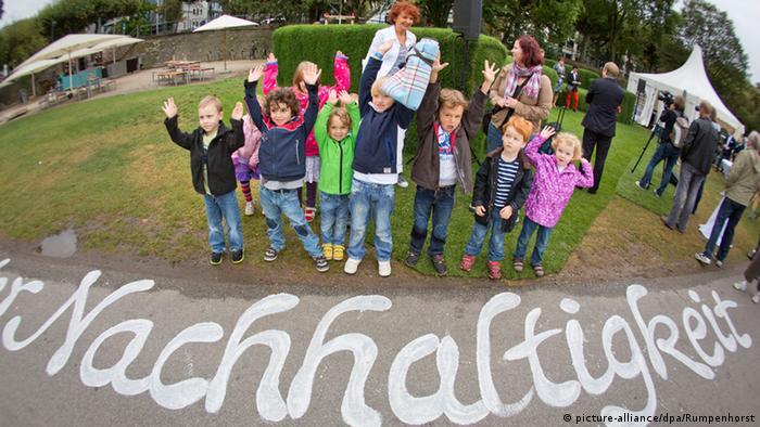 Eine Gruppe Kindergartenkinder steht vor dem Schriftzug Nachhaltigkeit