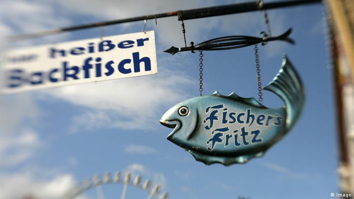 An einem Restaurant hängt ein Schild mit der Aufschrift Heißer Backfisch neben einem Fisch