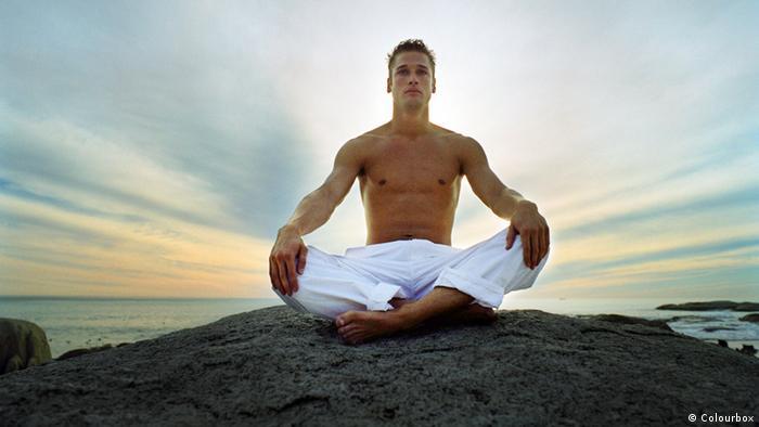 Mann sitzt meditierend auf Felsen