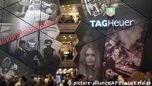Visitors pass the Tag Heuer booth, at the watch and jewelry show Baselworld in Basel, Switzerland, on Thursday, March 19, 2015. (AP Photo/Keystone,Georgios Kefalas)