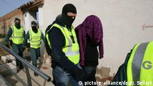 epa04088730 Spanish Civil Guard members detain one of the ten persons accused to be part of the Latin American gang known as 'Los Trinitarios' and seize a kilogram of cocaine in a neighborhood of Tarragona, Catalonia, Spain, 19 February 2014. In the operation have participated 150 Guardia Civil members helped by the local police of Tarragona and Salou. The detained are accused of drug traffic and belonging to a gang. EPA/JAUME SELLART