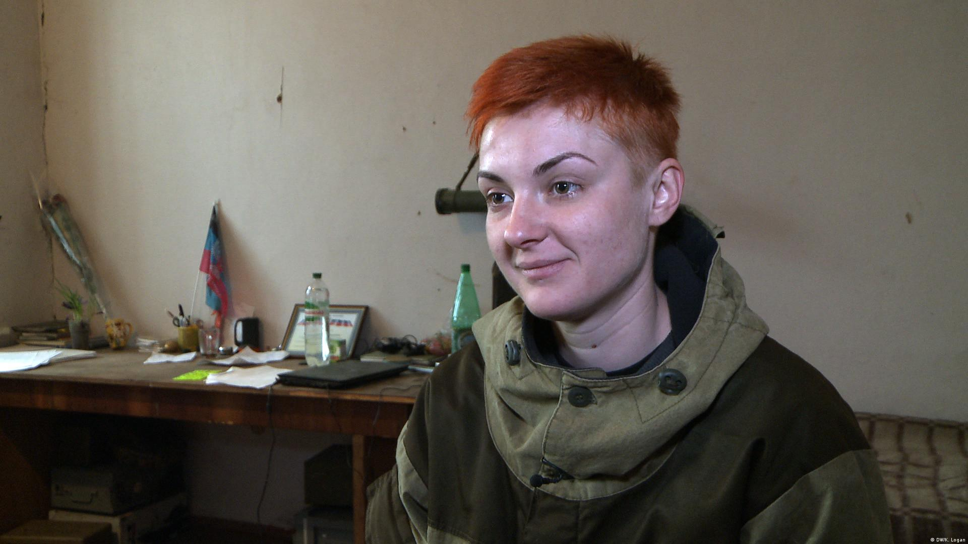 Ukraine separatist Nut, with red, close-cropped hair, smiles off-camera