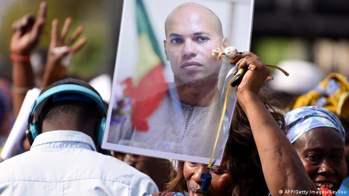 Treffen der Opposition inm Senegal Frau hält bild des ehemaligen Ministers Karim Wade hoch
