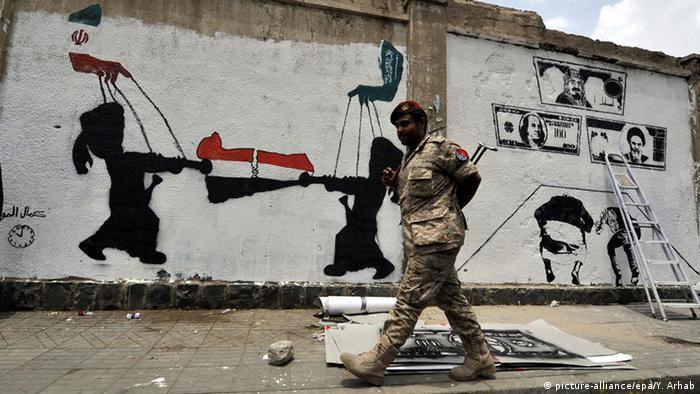 Seorang serdadu pemerintah Yaman berjalan melewati tembok bergambar grafiti yang menolak campur tangan asing di Sanaa.