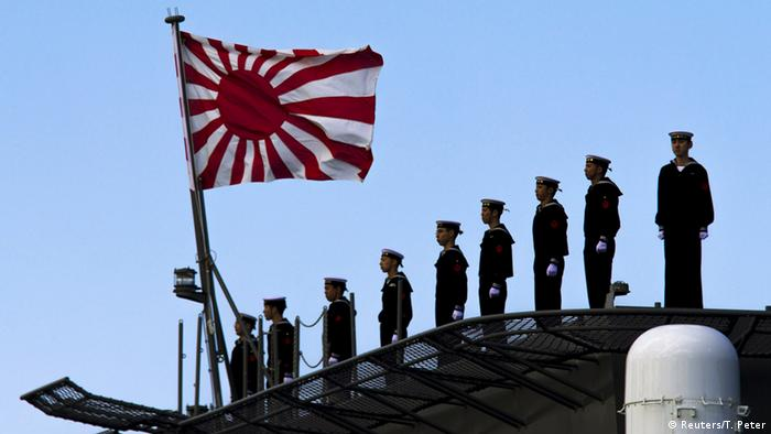 Japanese troops stand next to the flag