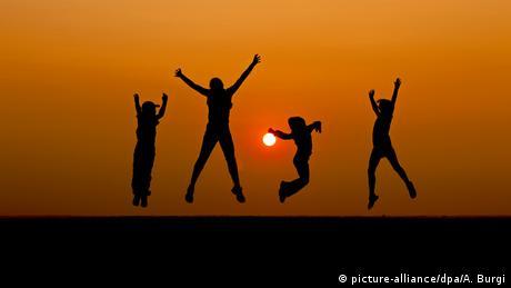 Vier Kinder hüpfen in die Luft. Hinter ihnen ist ein Sonnenuntergang zu sehen.