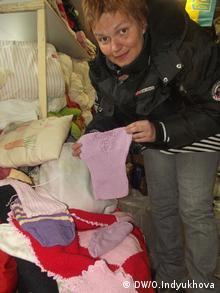Леся Литвинова показывает наборы для новорожденных, связанные датскими пенсионерами