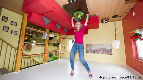 In einem Zimmer steht alles Kopf, eine Frau drückt scheinbar die Decke bzw. den Fußboden nach oben (picture-alliance/ZB/Sauer)