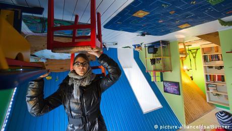 Eine Besucherin steht im Haus auf dem Kopf und balanciert scheinbar einen Stuhl über dem Kopf (picture-alliance/dpa/Büttner)
