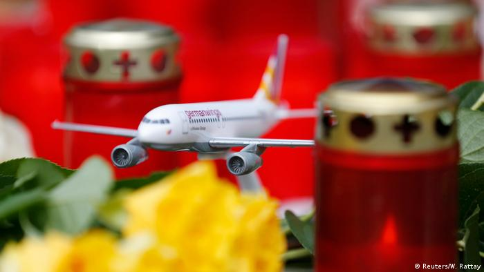 A model Germanwings airplane stands amongst candles outside the company's headquarters in Cologne Bonn airport March 27, 2015 (Photo: REUTERS/Wolfgang Rattay)