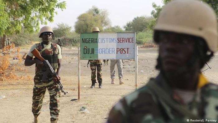 Nigerien soldiers walk past a customs signpost in Duji, Nigeria, March 25, 2015 (Photo: REUTERS/Joe Penney)