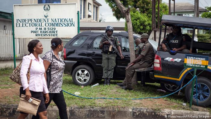 Two women walk past as uniformed soldiers guard the premises of Nigeria's Independent Electoral Commission in Port Harcourt