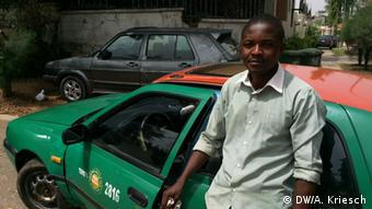 Taxi driver James Godspower standing near his green and red vehicle