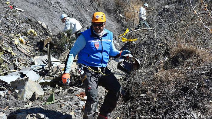 Homens trabalham em meio aos destroços do avião
