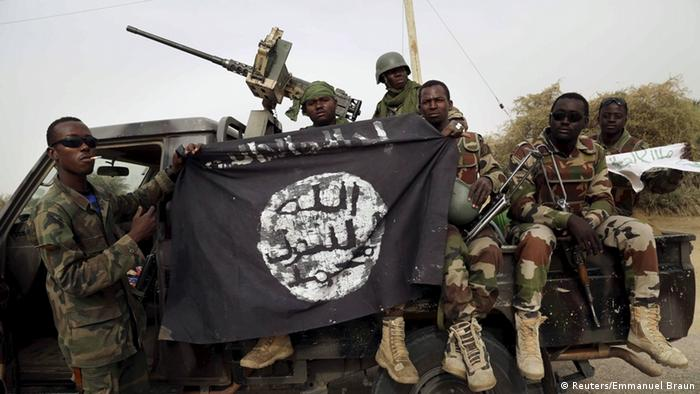 Nigerian soldiers hold a captured Boko Haram flag