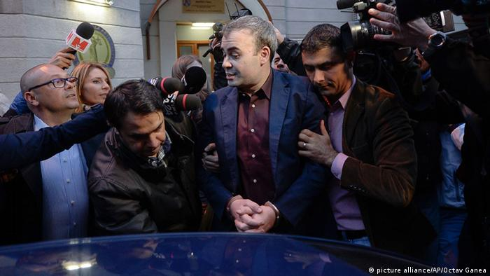 Former Romanian finance minister Darius Valcov leaves the prosecutors office in Bucharest, Romania. AP Photo/Octav Ganea, Mediafax