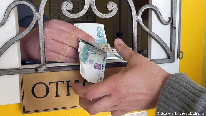 Ruble bills are handed through a window frill