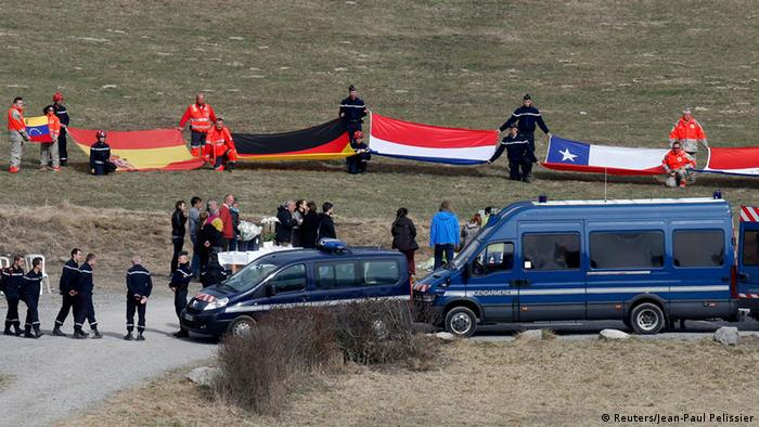 Flags representing some of the nationalities of the victims are seen as family members and relatives gather at the moemorial, near the crash site of a Germanwings Airbus A320