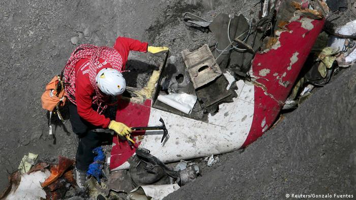 Helper examining debris from the crash. REUTERS/Gonzalo Fuentes