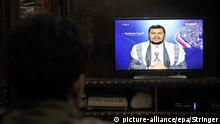 epa04571595 A Yemeni watches Shiite Houthi rebel commander Abdel-Malik al-Houthi delivering a speech on a pro-Shiite Houthi group Al-Maseera television, in Sana'a, Yemen, 20 January 2015. Yemeni rebel leader Abdul-Malik al-Houthi accused President Abd Rabu Mansour Hadi of having protected the corrupt. Hadi also failed to make any serious effort to implement a UN-brokered peace deal he signed with the Houthis in September 2014, the rebel leader said in a speech broadcast on his movement's television channel on 20 January. EPA/STRINGER +++(c) dpa - Bildfunk+++