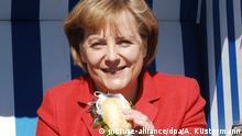 Bundeskanzlerin Angela Merkel (CDU) sitzt am Samstag (02.05.2009) mit einem Heringsbrötchen im Restaurant Moby Dick im Sassnitzer Hafen. Die Kanzlerin hat als Bundestagsabgeordnete ihren Wahlkreis auf Rügen. In Nordvorpommern wird gern Fisch gegessen und in Sassnitz wird er täglich frisch angelandet. Der frühere Steigenberger-Spitzenkoch Holger Nebel hat in seinem Restaurant Moby Dick eine ganz besondere Art, Matjes mit Kräutern oder Bismarckhering im warmen Brötchen zuzubereiten. Foto: Andreas Küstermann dpa/lmv +++(c) dpa - Bildfunk+++