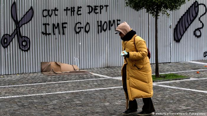 A woman walks past graffiti that reads 'Cut the debt IMF go home' on a fence around the Academy of Sciences in Athens