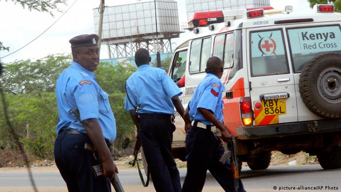 Kenyan police officers take positions outside the Garissa University College as an ambulance carrying the injured going to a hospital, during an attack by gunmen in Garissa, Kenya, Thursday, April 2, 2015. . (AP Photo) (AP Photo)
