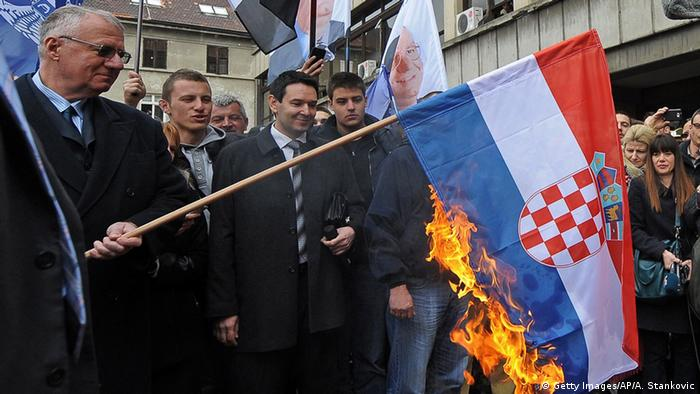 Seselj burning a Croatian flag