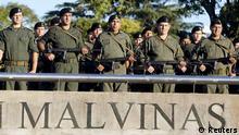 A row of Gendarmerie officers pay tribute to the Argentine servicemen who died in the1982 Falklands War between Britain and Argentina on the 33rd anniversary of the war over the island chain in Rosario April 2, 2015. Britain should spend more helping its own poor than on defending the Falkland Islands, President Cristina Fernandez de Kirchner said on Thursday, responding to a recently-announced budget increase aimed at protecting the contested archipelago. Britain's government said last week it would reinforce its military presence on the Falklands to counter the very live threat posed by Argentina. Fernandez, in a speech honouring soldiers who died in her country's failed 1982 invasion of the South Atlantic islands, dismissed the idea of Argentina being a threat, telling Britain to focus instead on fighting poverty within its own borders. REUTERS/Enrique Marcarian