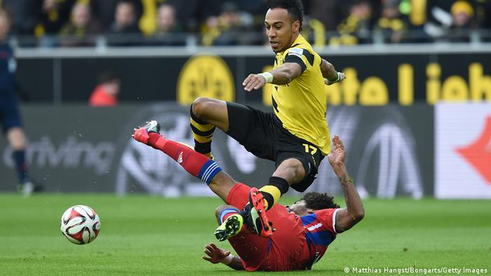 A Dortmund player is brought down by a Bayern defender