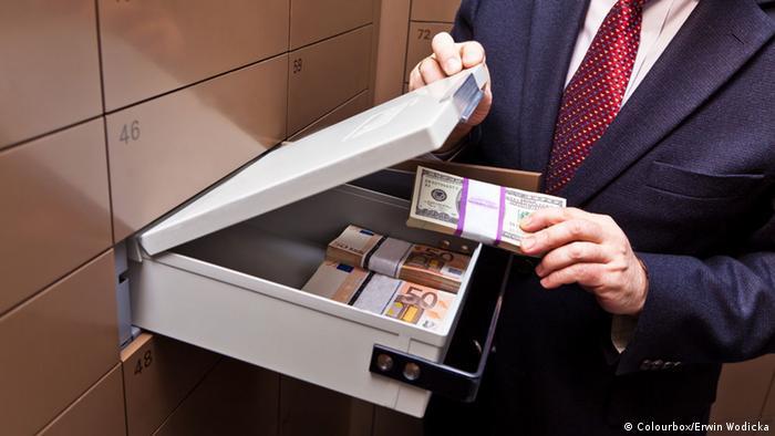 Символ коррупции - ячейка в банке, куда человек кладет пачки банкнот