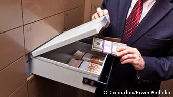 Человек с чемоданом, в котором лежат пачки долларов и евро
