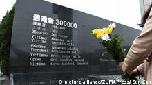 A person holds a bunch of flowers at the Nanjing memorial, archive image from 2015 (picture alliance/ZUMAPress/ Sun Can)