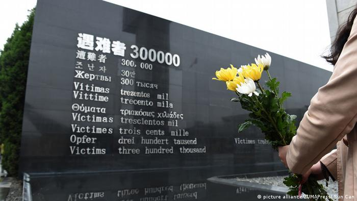 A person holds a bunch of flowers at the Nanjing memorial, archive image from 2015