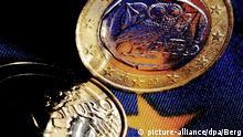 ARCHIV - ILLUSTRATION - Griechische Euro-Münzen stehen am 07.01.2015 in Köln (Nordrhein-Westfalen) auf einer EU-Fahne. Griechenland braucht Geld, die Geldgeber wollen Reformen sehen. In diesem Spannungsfeld bewegen sich die Verhandlungen zwischen Athen und den Europartnern. Was wie Stillstand wirkt, ist langsamer Fortschritt, meinen Experten. Foto: Oliver Berg/dpa (zu dpa-KORR.: Endspurt ohne Ende? Griechenlands Verhandlungen mit den Europartnern vom 04.04.2015) +++(c) dpa - Bildfunk+++