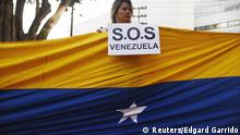 A woman holds a sign while standing behind a Venezuelan flag during a protest in Panama City April 8, 2015. Venezuelan residents in Panama gathered to protest against Venezuela's President Nicolas Maduro's government ahead of his arrival for the Summit of the Americas. REUTERS/Edgard Garrido