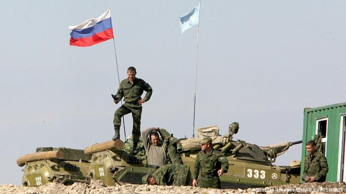 A Russian soldier stands under a Russian flag in South Ossetia in 2008 (picture-alliance/ZURAB KURTSIKIDZE)