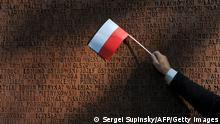 A person waves a Polish flag at the Monument dedicated to Polish officers, murdered in the 1940 Soviet-era Katyn massacre, in Kharkiv on September 25, 2010. Komorowski and Ukrainian Prime Minister Mykola Azarov joined about 300 relatives of the killed officers to lay wreaths at the memorial. AFP PHOTO/ SERGEI SUPINSKY (Photo credit should read SERGEI SUPINSKY/AFP/Getty Images)