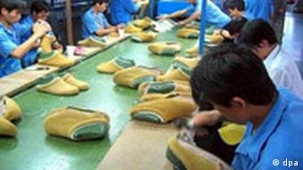 People working on a conveyor belt in a shoe factory in China