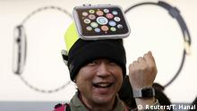 A man wearing cardboard hat depicting an Apple Watch, reacts as he tries on the watch after it went on display the Apple Store at Tokyo's Omotesando shopping district April 10, 2015. Apple Inc expects tremendous interest for its new smartwatch and demand to outstrip supply as consumers get an up-close look on Friday at CEO Tim Cook's first major product. REUTERS/Toru Hanai TPX IMAGES OF THE DAY