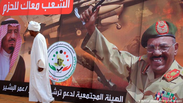 A man walks past an election poster showing President Omar al-Bashir